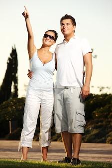 公園を散歩している若い素敵なカップル。女の子は何かを指差して笑っています。