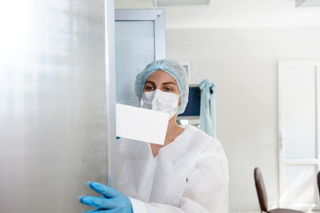 보호복 모자 마스크와 장갑을 낀 젊은 간호사가 의료실 사물함에서 문서를 가져옵니다.