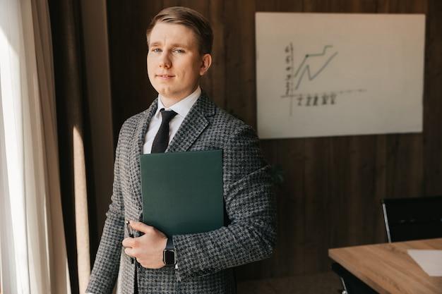 공정한 피부를 가진 젊은 회사원이 문서가 담긴 폴더를 손에 들고 사무실에 선다. 남자는 사무실에서 일합니다.