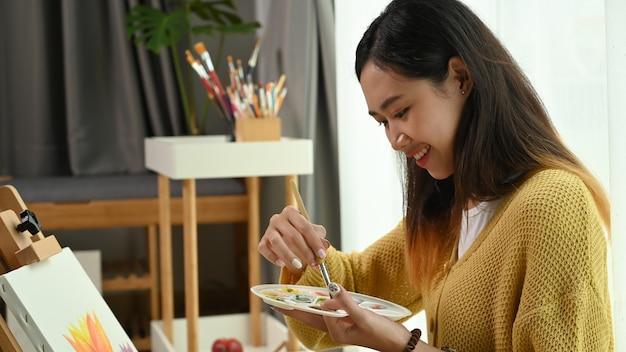 Молодой художник улыбается и работает над живописью в мастерской