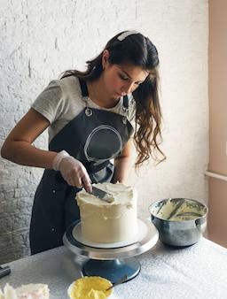 회색 앞치마를 입은 젊은 생과자 요리사 소녀가 부엌에서 케이크를 만듭니다.