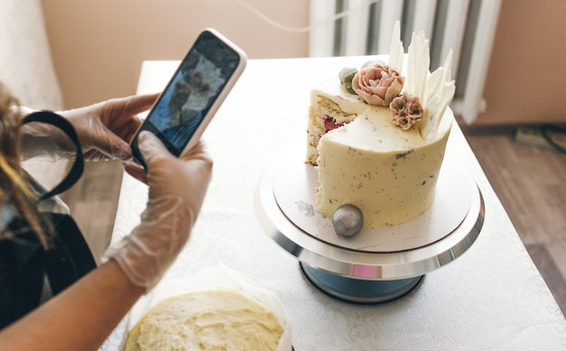 회색 앞치마를 입은 젊은 생과자 요리사 소녀가 준비된 케이크의 사진을 찍습니다.
