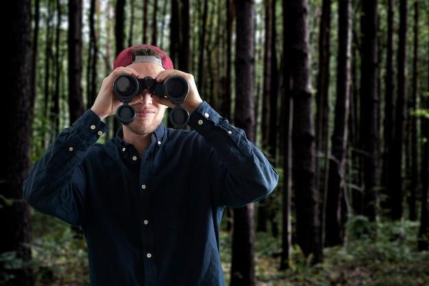 山でハイキングし、双眼鏡を使用して、旅行の概念を若い人