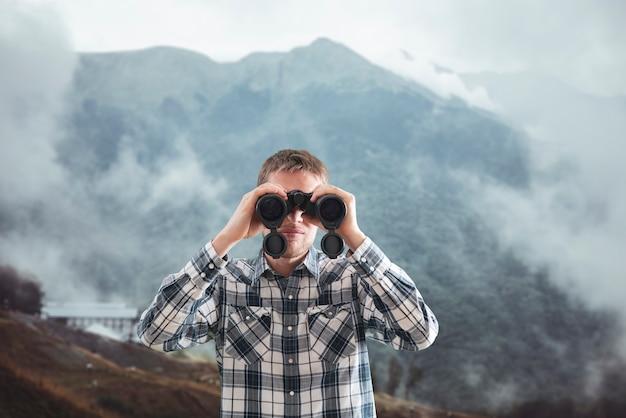 산에서 하이킹을하고 쌍안경을 사용하는 젊은 사람, 여행 개념