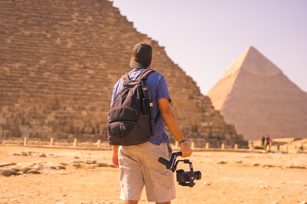 クフ王のピラミッドで最大のピラミッドの若い写真家。ギザのピラミッドは、世界最古の葬式の記念碑です。エジプト、カイロ市