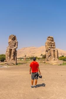 Молодой фотограф осматривает две египетские скульптуры в городе луксор на берегу нила. египет