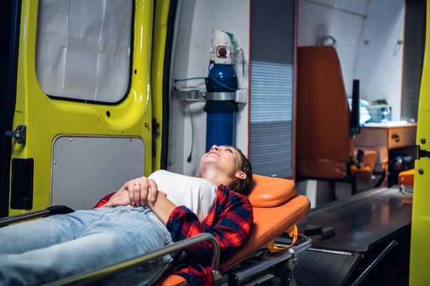 Молодая позитивная женщина лежит на носилках перед машиной скорой помощи