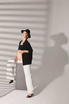 Молодая беременная модель в модном наряде позирует в белой студии с тенями на заднем плане