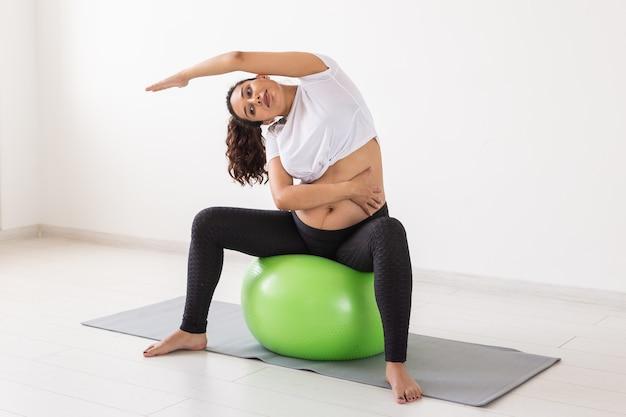 Молодая беременная женщина делает упражнения с фитнес-мячом, сидя на коврике