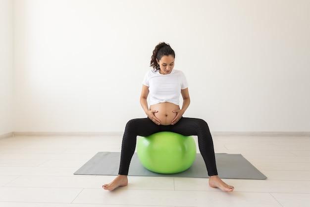 Молодая беременная женщина делает упражнения на расслабление с помощью фитнес-мяча, сидя на коврике