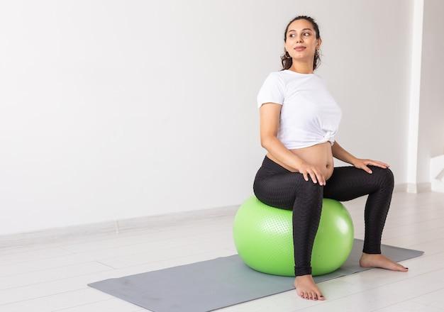 매트에 앉아있는 동안 피트니스 공을 사용하여 이완 운동을하는 젊은 임산부