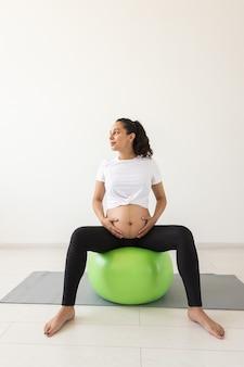 매트에 앉아 있는 동안 피트니스 공을 사용하여 이완 운동을 하는 젊은 임산부