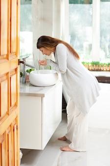 Молодая беременная женщина в ярко освещенной ванной моет утреннюю рутину уход за собой