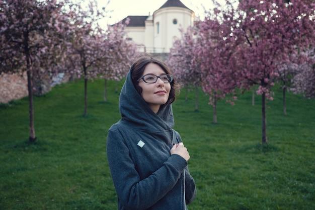 Молодая беременная женщина в саду у сакура в центре варшавы.