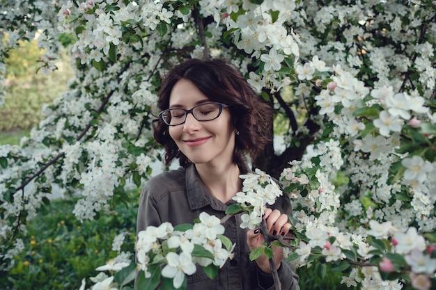 Молодая беременная женщина в яблоневом саду в центре варшавы.