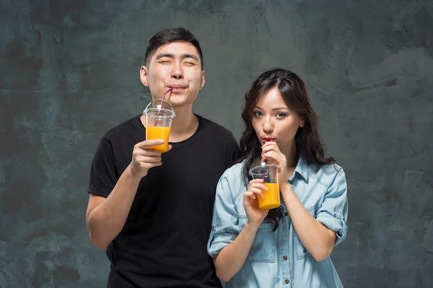 오렌지 주스의 안경 젊은 예쁜 아시아 부부