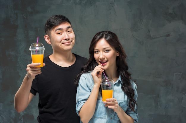オレンジジュースのグラスを持つ若いかなりアジアのカップル