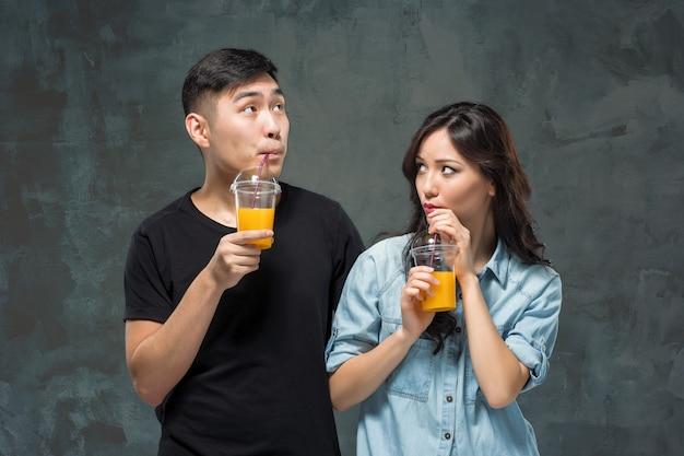 灰色のスタジオの背景で手にオレンジジュースのガラスを持つ若いかなりアジアの女性。