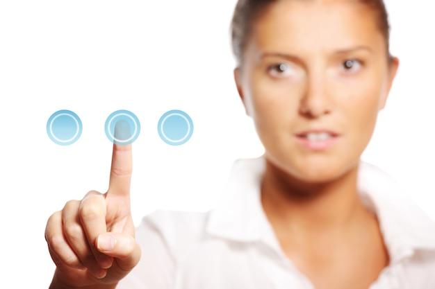 Молодая красивая деловая женщина, касаясь кнопки на белом фоне