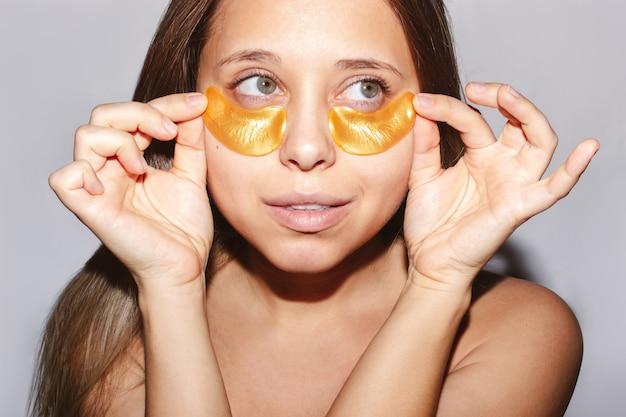 若いかなり白人のブロンドの女性は彼女の目の下の皮膚に金のパッチを置き、目をそらします