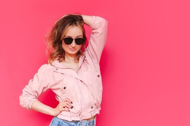 Молодая довольно уверенная в себе кавказская женщина с каштановыми волосами в повседневной стильной куртке и черных солнцезащитных очках позирует, положив руку на голову на ярко-розовой стене
