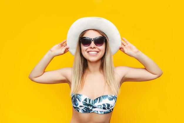 Молодая симпатичная кавказская улыбающаяся блондинка в солнечных очках с белой шляпой и купальником рада предстоящему отпуску, изолированному на ярко-желтой стене