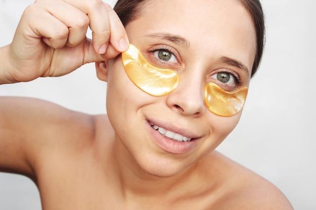 若いかなり白人の笑顔の女性は彼女の目の下の皮膚に金のパッチを置きます
