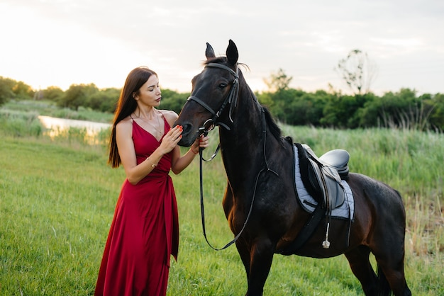 Молодая симпатичная девушка в красном платье позирует на ранчо с породистым жеребцом на закате. любовь и забота о животных.