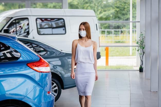 Молодая симпатичная девушка осматривает новую машину в автосалоне в маске во время пандемии. купля-продажа автомобилей в период пандемии.