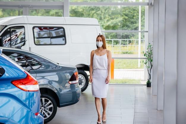 パンデミックの最中に、若いかわいい女の子がマスクをかぶった自動車販売店で新車を検査します。パンデミックの時期における自動車の売買。