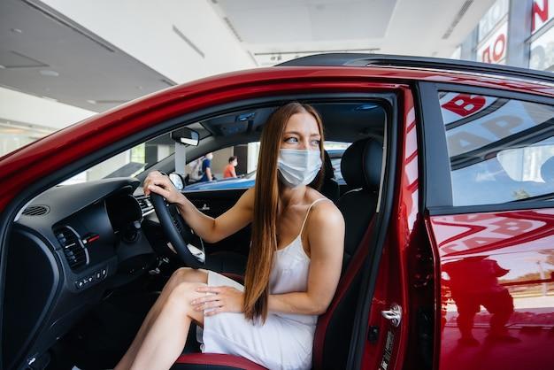 Молодая симпатичная девушка в маске осматривает новую машину в автосалоне во время пандемии. купля-продажа автомобилей в период пандемии.