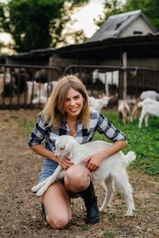 山羊や他の動物と牧場でポーズをとる若いかわいい女の子。農業、畜産。