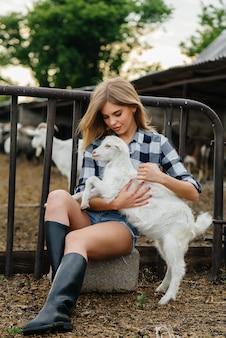 ヤギや他の動物と一緒に牧場でポーズをとる若いかわいい女の子