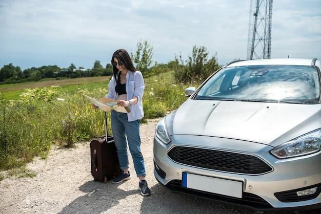 若いきれいな女性が地図上で最良の方法を探して彼女の車のそばに立っています