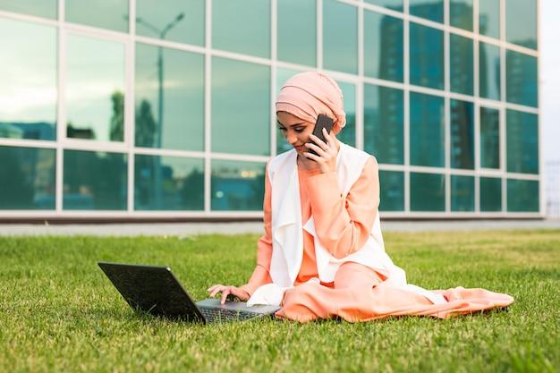 Молодая красивая мусульманская бизнес-леди в парке во время разговора по смартфону, глядя на ноутбук