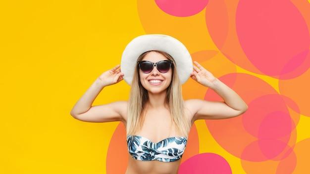 선글라스를 끼고 웃고 있는 젊고 예쁜 금발 여성은 다가오는 휴가에 대해 행복하다