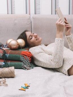 Молодая симпатичная женщина в легком свитере сидит на кровати с елочными украшениями и читает письмо