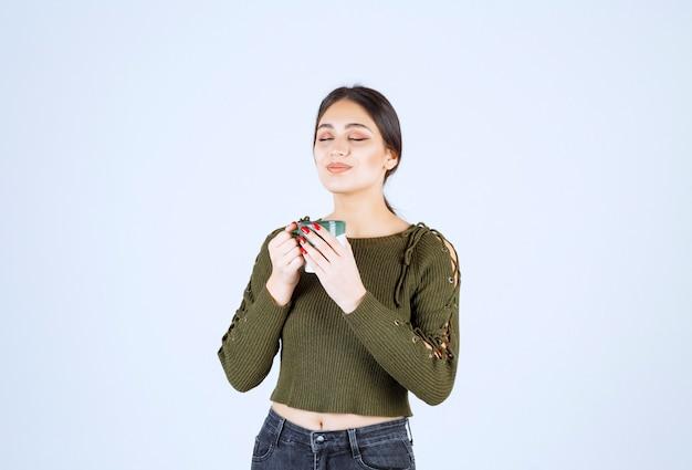Модель молодой красивой женщины, наслаждаясь чашкой горячего чая