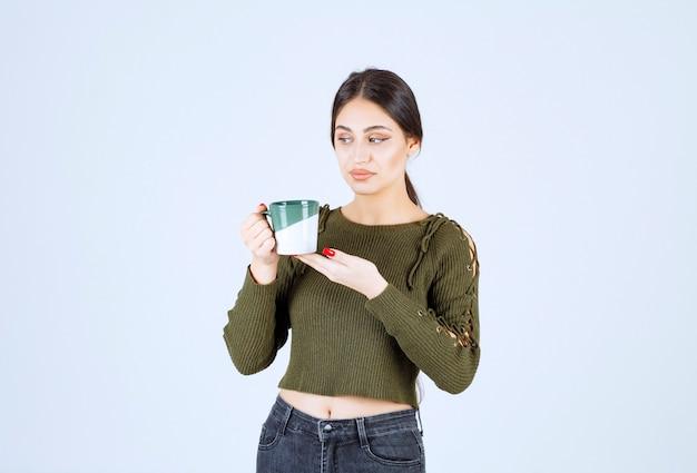 컵을 들고 멀리 찾고 젊은 예쁜 여자 모델.