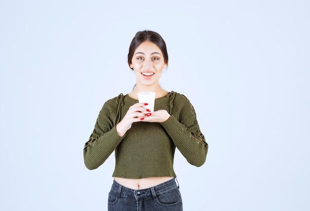 뜨거운 음료와 플라스틱 컵을 들고 젊은 예쁜 여자 모델.