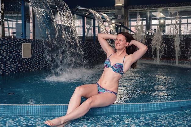 若いきれいな女性がプールでリラックスします。自由の概念。スパとリラックス、女性の幸せ。ウェルネスリゾートのインテリア。