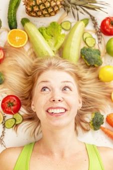 Молодая красивая женщина в окружении овощей и фруктов