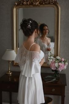 레이스 peignoir에 신부 머리 장식을 한 젊고 예쁜 여자가 거울 앞에서 아름다운 포즈를 취하고 있습니다.