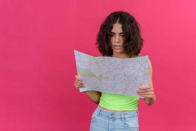 Молодая красивая женщина с короткими волосами в зеленых тонах удивленно смотрит на карту
