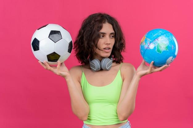Молодая красивая женщина с короткими волосами в зеленом топе в наушниках держит глобус и футбольный мяч