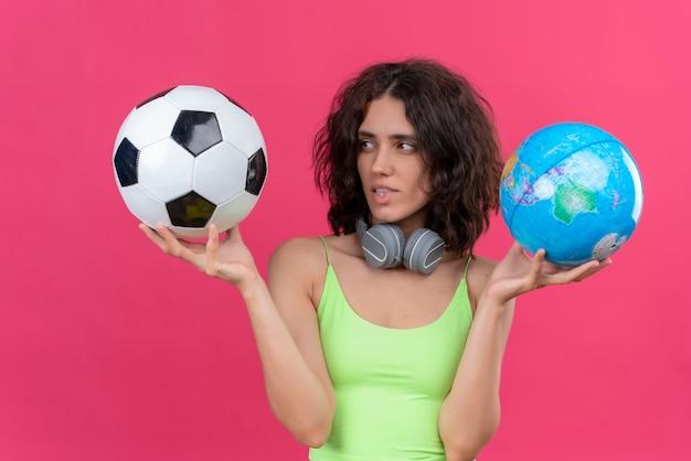 Молодая красивая женщина с короткими волосами в зеленом топе в наушниках держит глобус и смотрит на футбольный мяч