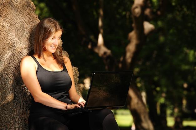 公園でラップトップに取り組んでいる若いきれいな女性