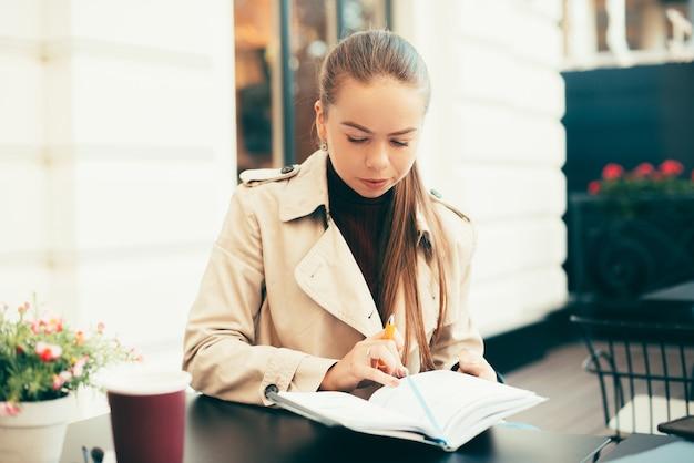 生産的な若い女性がカフェでプランナーに書いています