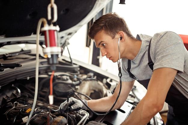 Молодой квалифицированный механик ищет неисправности на работе в автосервисе.