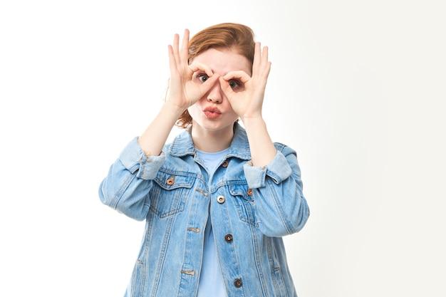 Молодая рыжеволосая женщина показывает руками очки, смотрит прямо в камеру, что-то ищет. портрет смешной девушки в джинсах на белом фоне